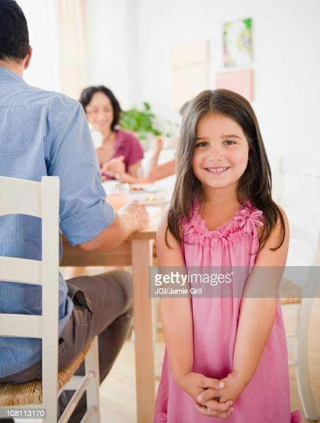 Smiling girl with family at dinner table behind her