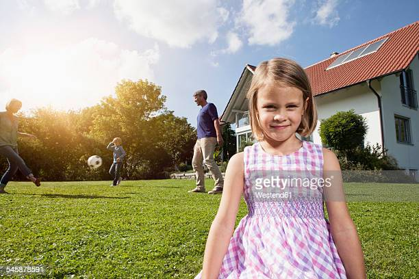 Smiling girl with family playing soccer in garden