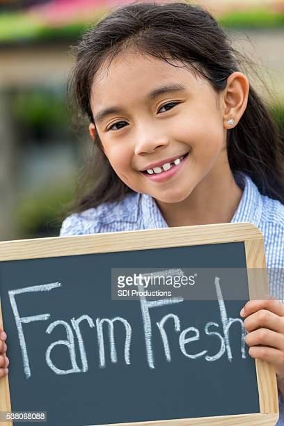 Smiling girl with Farm Fresh sign