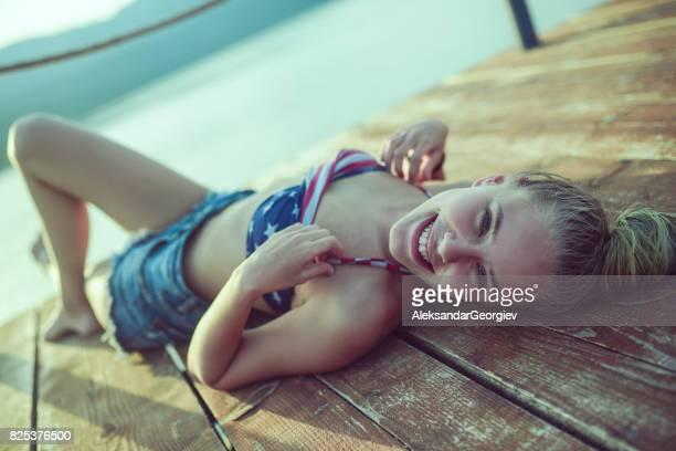 Smiling Girl With Hair Bun lying on Lake Pier Sunbathing