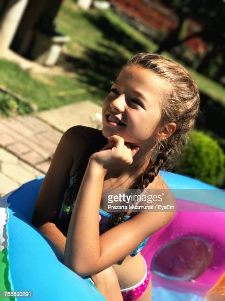 Smiling Girl With Hand On Chin Looking Away In Paddling Pool During Sunny Day