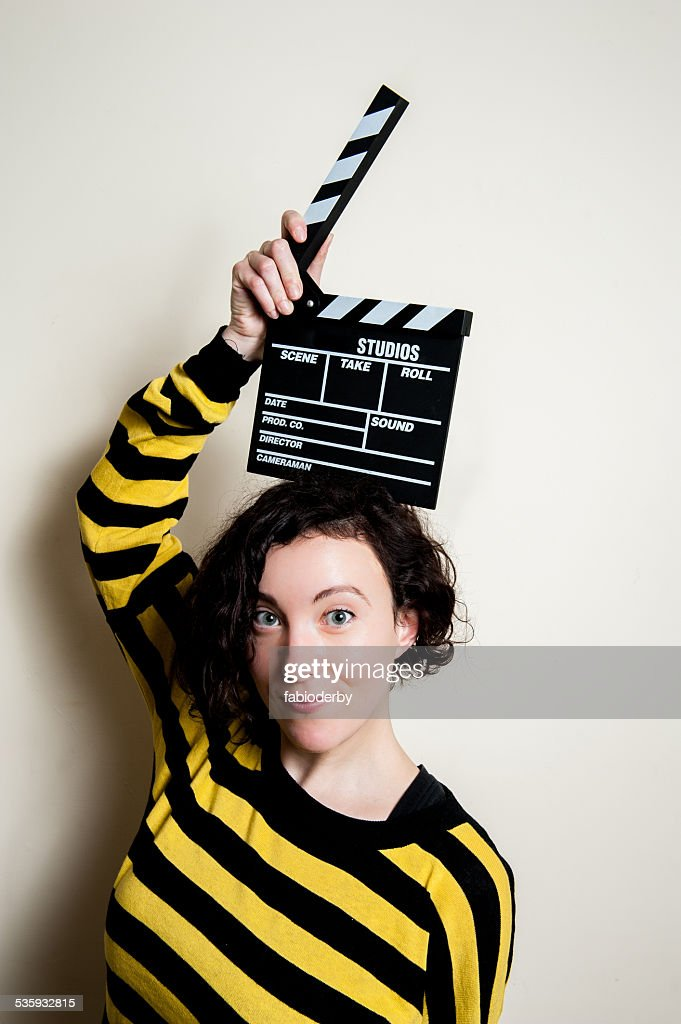 Smiling girl with movie clapper on white background : Stock Photo
