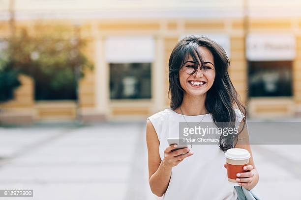 Smiling girl with smart phone and coffee cup