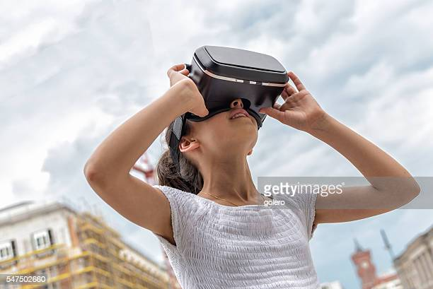 smiling girl with virtual reality simulator outdoors looking
