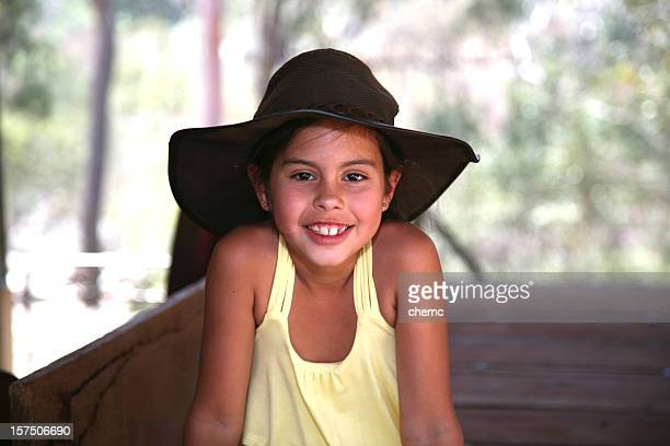 Smiling girl with yellow tank top and cowboy hat outside