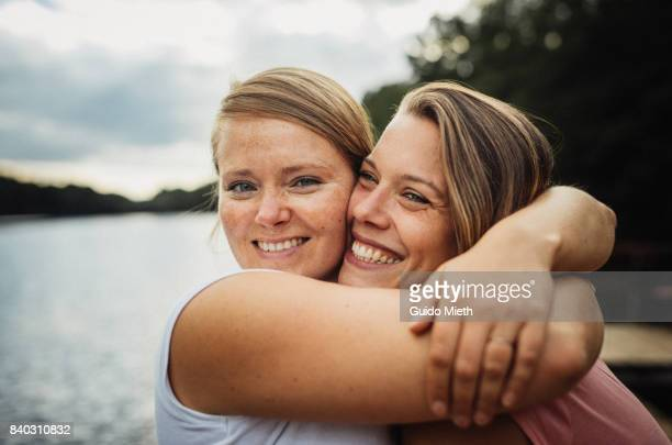 Smiling girlfriends hugging.