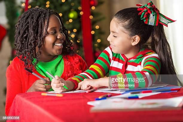 Smiling girls making Christmas cards together