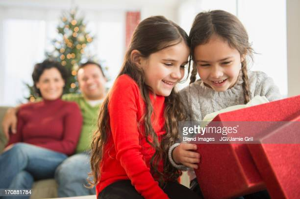 Smiling girls opening Christmas present