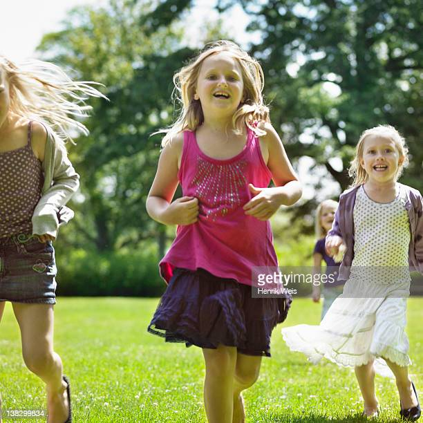 Smiling girls running in field