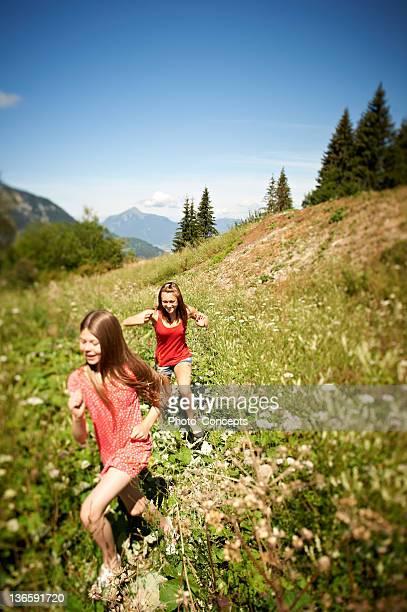 Souriant filles courir en Grande plante herbacée