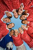 Smiling Girls Soccer Team in Huddle