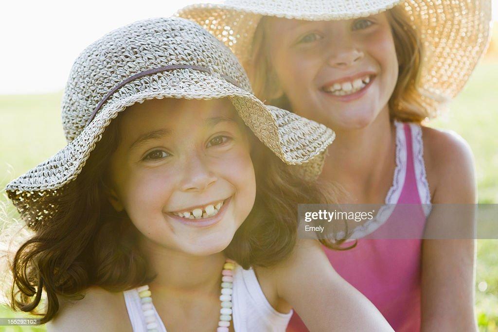 Smiling girls wearing sunhats outdoors : Stock Photo