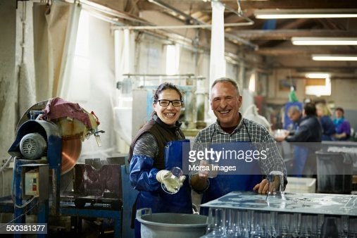 Smiling glass workers in factory