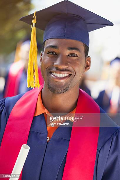 Smiling graduate holding diploma
