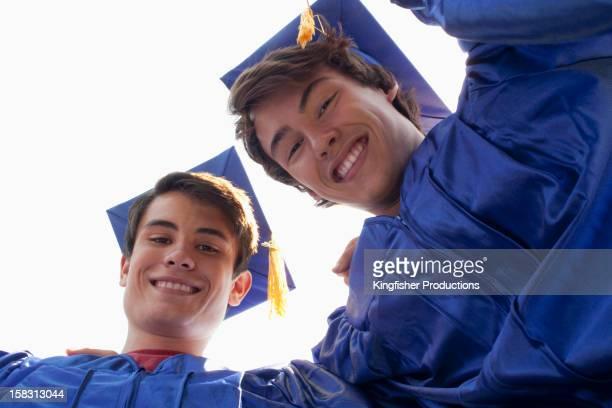 Smiling graduates bending to look at camera