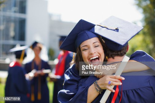 Lächelnd Absolventen umarmen im Freien