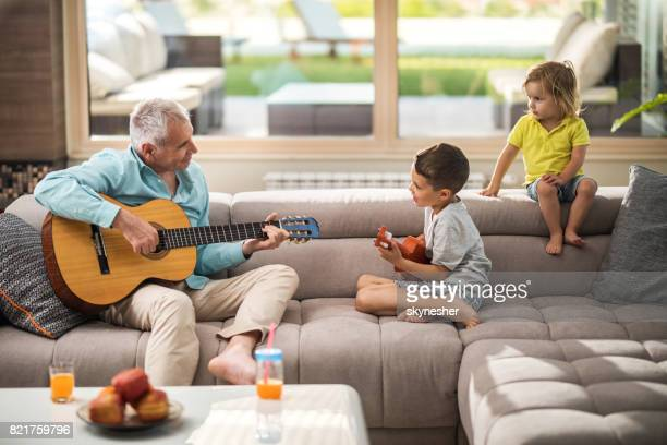 Smiling grandfather and grandkids playing acoustic guitar on the sofa.