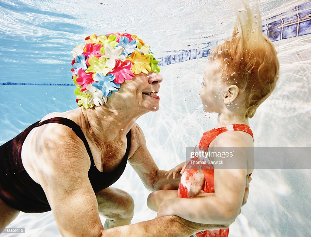 Smiling grandmother and granddaughter underwater