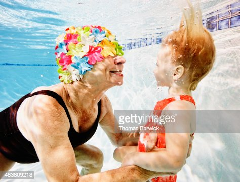 Smiling grandmother and granddaughter underwater : Foto de stock