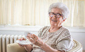 Smiling grandmother drinking coffee at home.