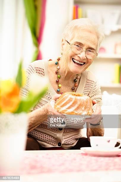 Lächeln Großmutter, die einen Kuchen