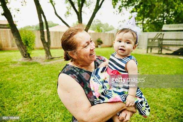 Smiling grandmother holding granddaughter during her first birthday party