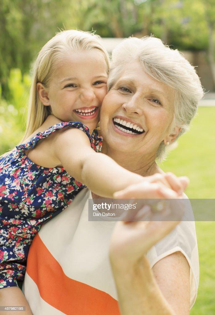 Smiling grandmother holding granddaughter