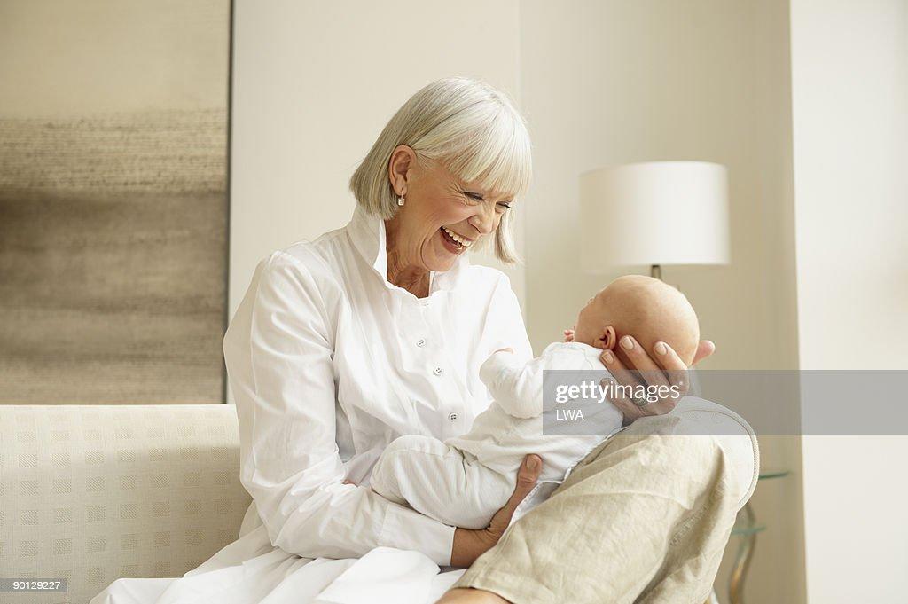 Smiling Grandmother Holding Infant Grandson : Stock Photo