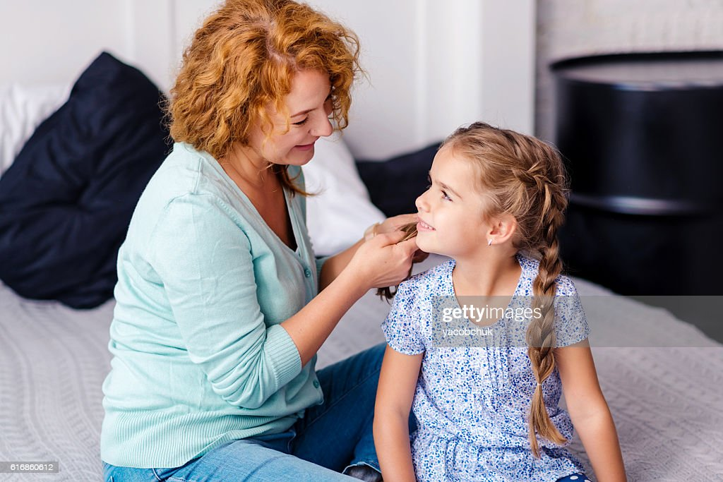 Smiling grandmother plaiting braids to her granddaughter : Stock Photo