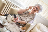 Smiling grandmother talking on landline rotary phone while sitting on armchair at home.