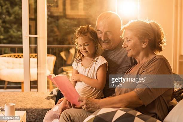 Lächelnd Großeltern beim Buchlesen ihrer Enkelin zu Hause fühlen.
