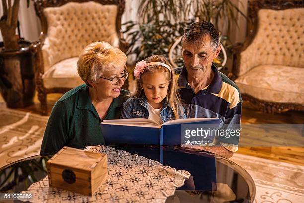 Lächelnd Großeltern storytelling ihrer Enkelin zu Hause fühlen.