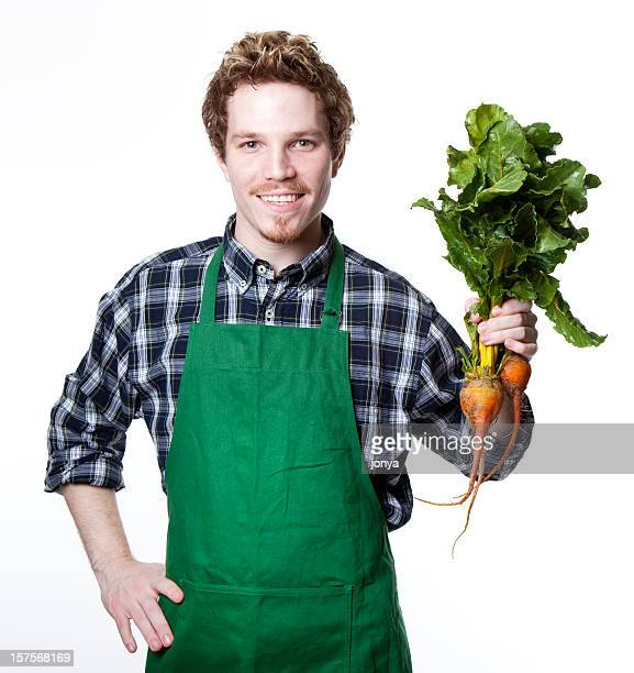 smiling green grocer holding up bunch of fresh beets