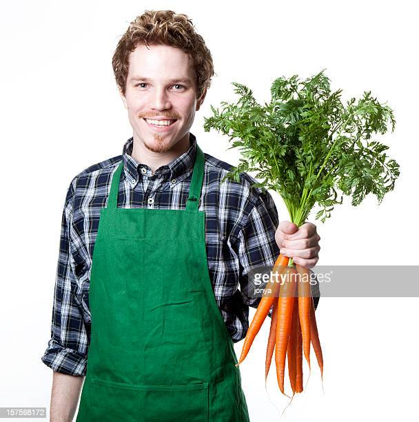 smiling green grocer with bunch of carrots
