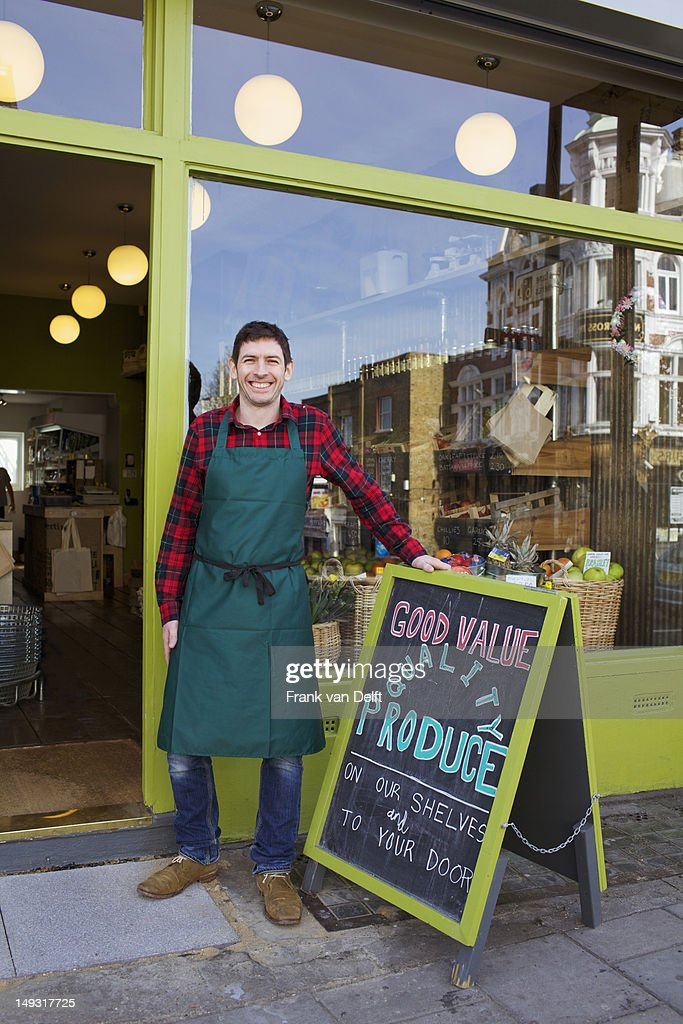 Smiling grocer standing outside store : Stock Photo