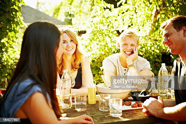 Smiling group of friends dining in backyard