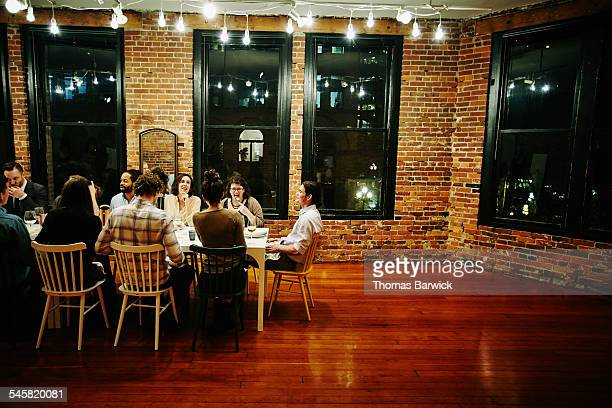 Smiling group of friends dining together in loft