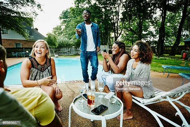 Smiling group of friends hanging out by pool