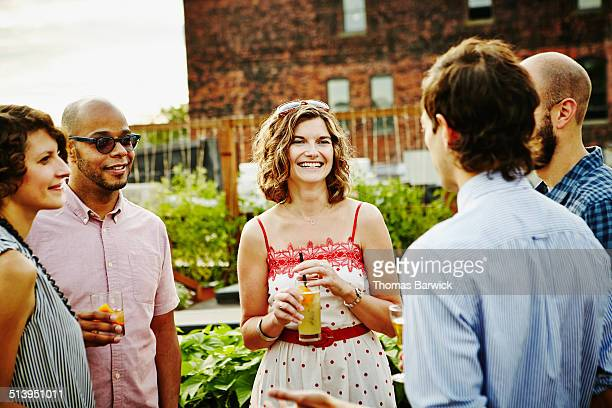 Smiling group of friends having drinks on rooftop