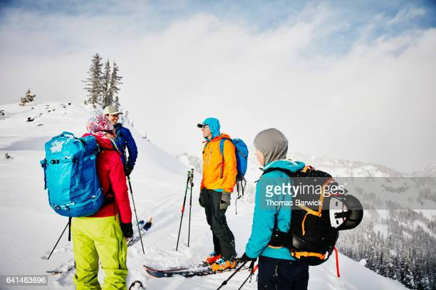 Smiling group of friends on backcountry ski tour standing on mountain peak