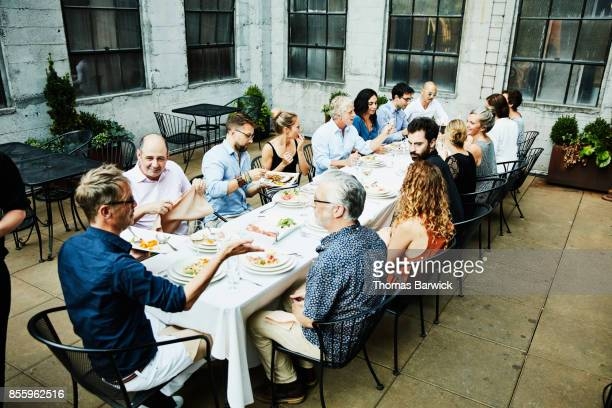 Smiling group of friends seated on outdoor patio sharing celebration dinner