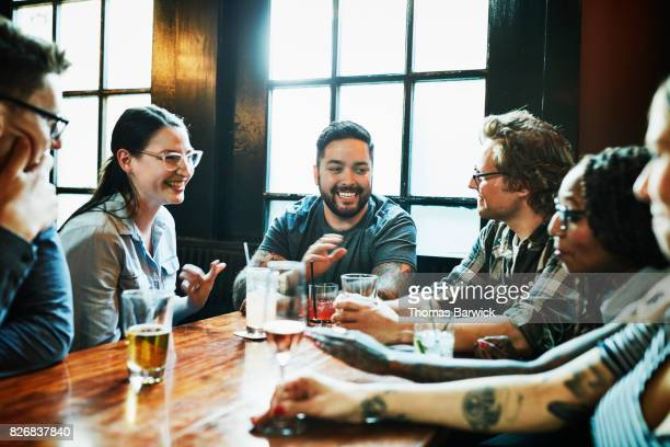 Smiling group of friends sharing drinks in bar