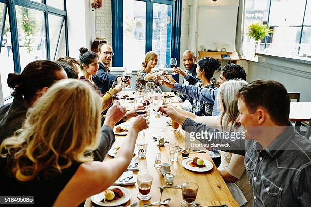 Smiling group of friends toasting at dinner party