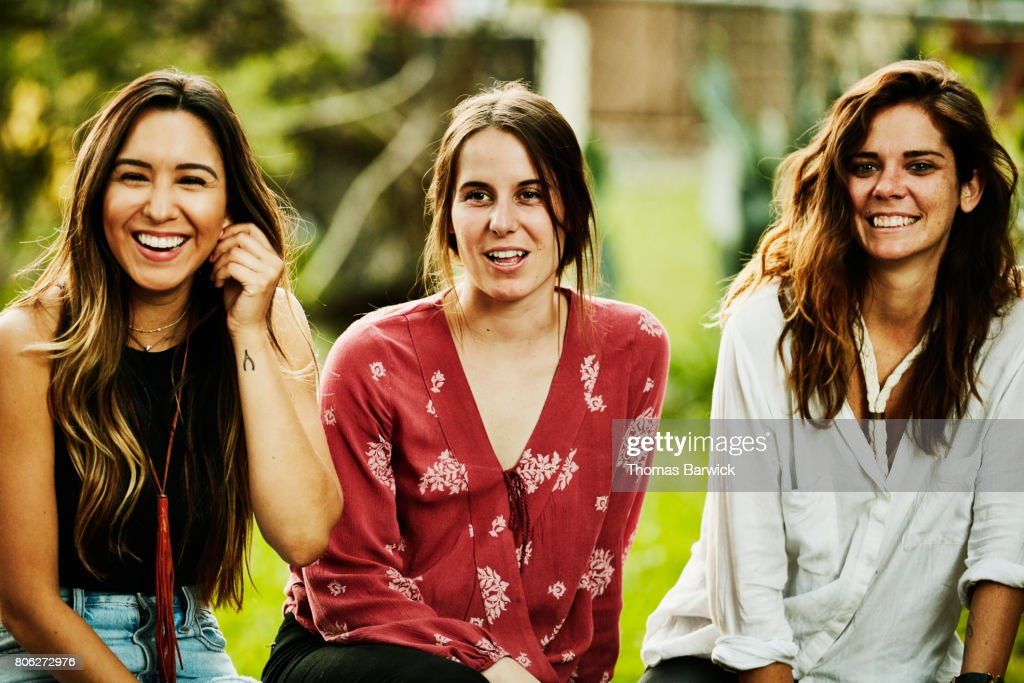 Smiling group of women hanging out together in backyard on summer evening : Stock Photo