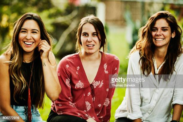 Smiling group of women hanging out together in backyard on summer evening