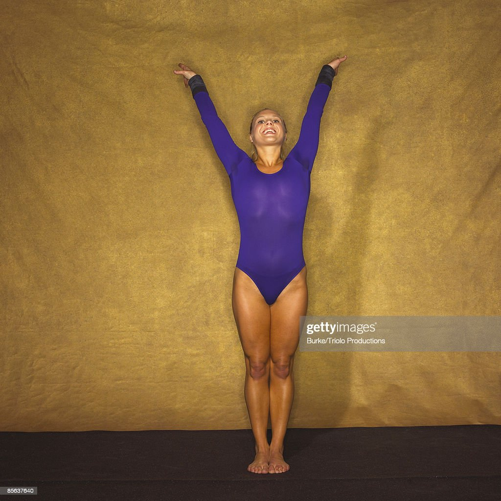 Smiling gymnast with arms raised : Stock Photo