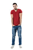 Smiling handsome casual man with hands in pockets looking at camera. Full body length portrait isolated over white studio background.