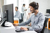Smiling handsome customer support operator agent with hands-free device working in call center