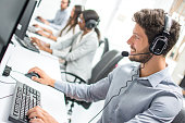 Smiling handsome male customer support phone operator with headset working in call centre.