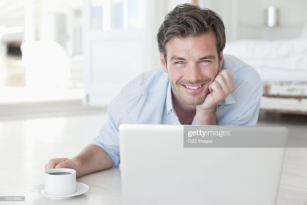 Smiling handsome man using laptop in bedroom : Stock Photo